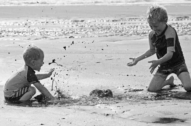 小男孩兄弟儿童使用,飞溅搅浊在海滩 免版税库存图片