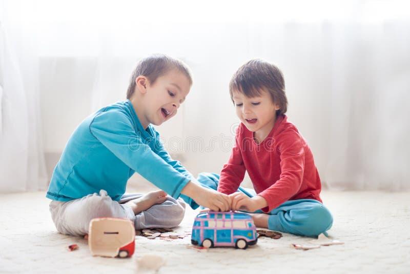 小男孩兄弟,打破他们的存钱罐买m的礼物 图库摄影