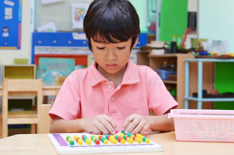 小男孩别针的研究颜色由montessori教育席子制成 免版税库存图片