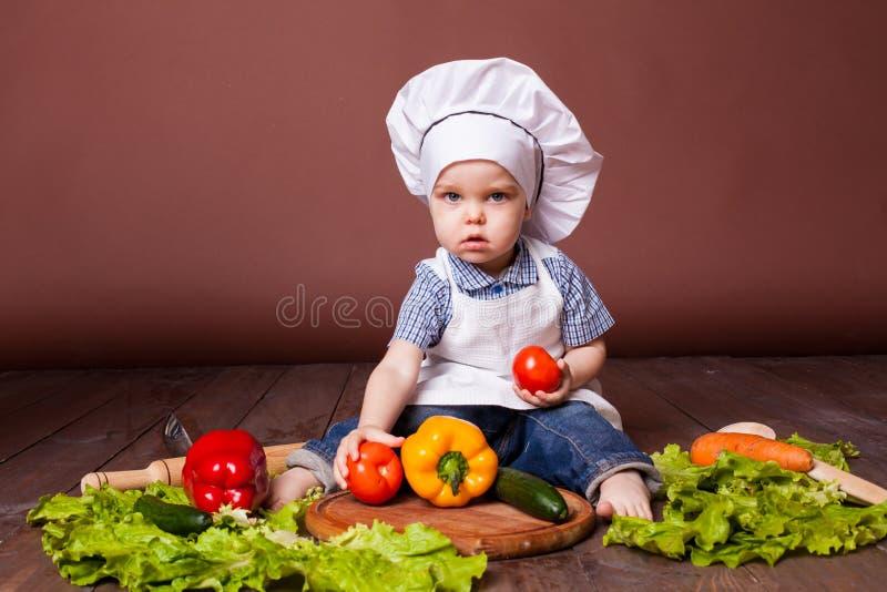 小男孩厨师红萝卜,胡椒,蕃茄,莴苣, 库存照片