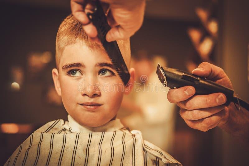 小男孩参观的发式专家 免版税库存照片