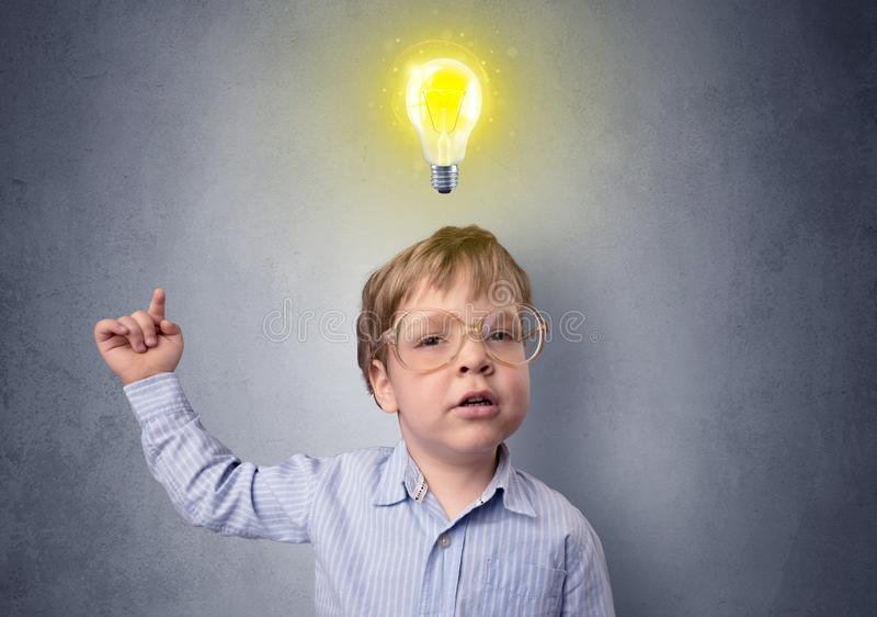 小男孩反复思考与在他的头上的电灯泡 库存照片