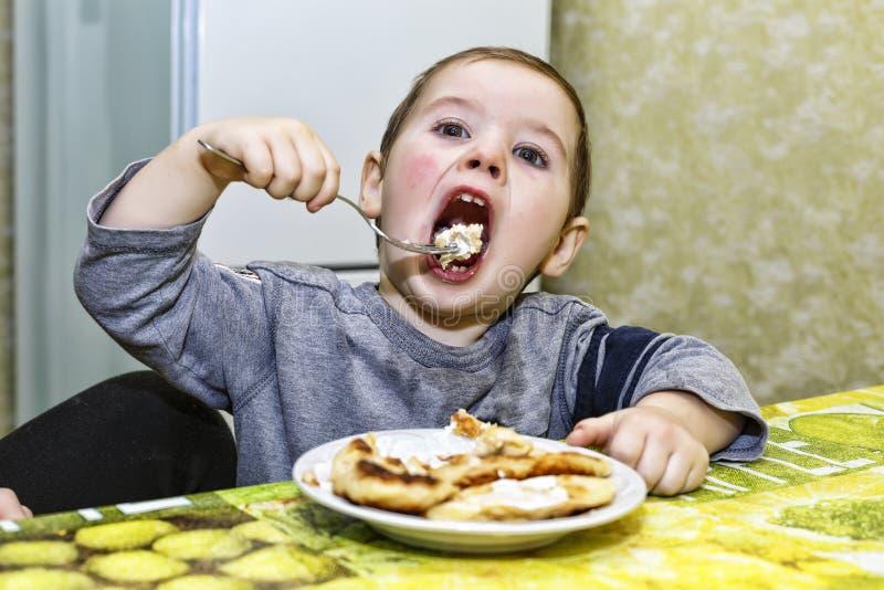 小男孩吃着 概念:健康孩子,愉快的童年 免版税库存图片
