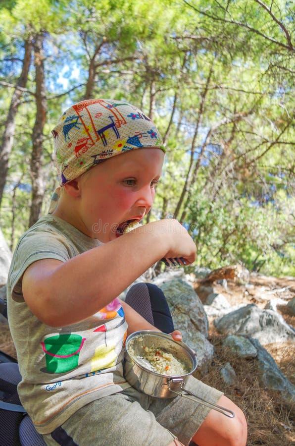 小男孩吃谷物室外在夏天 免版税库存照片