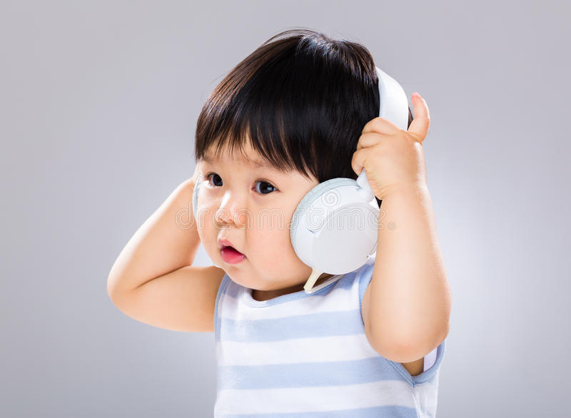 小男孩听音乐和拿着耳机 免版税库存图片