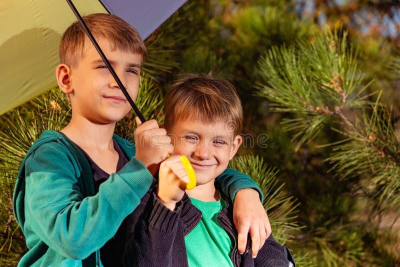 小男孩和他的哥哥是在一把明亮的多彩多姿的伞下 免版税库存照片
