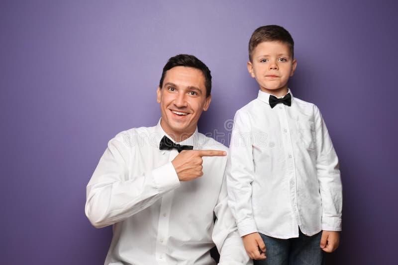 小男孩和他的父亲画象经典衬衣的在颜色背景 免版税库存图片