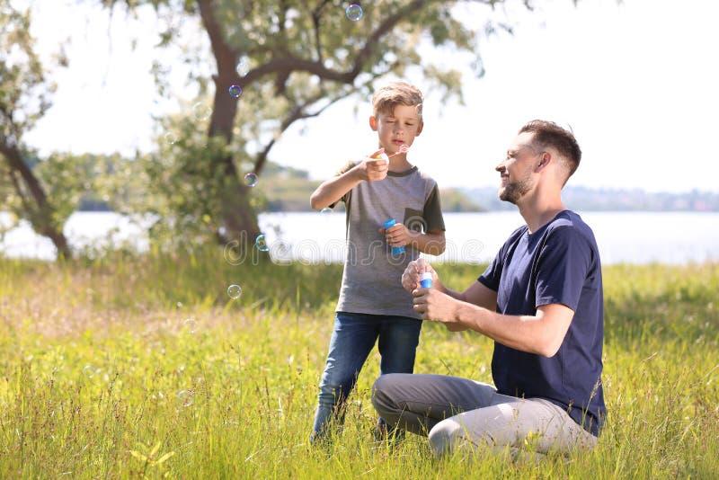 小男孩和他的爸爸吹的肥皂泡户外 免版税库存照片