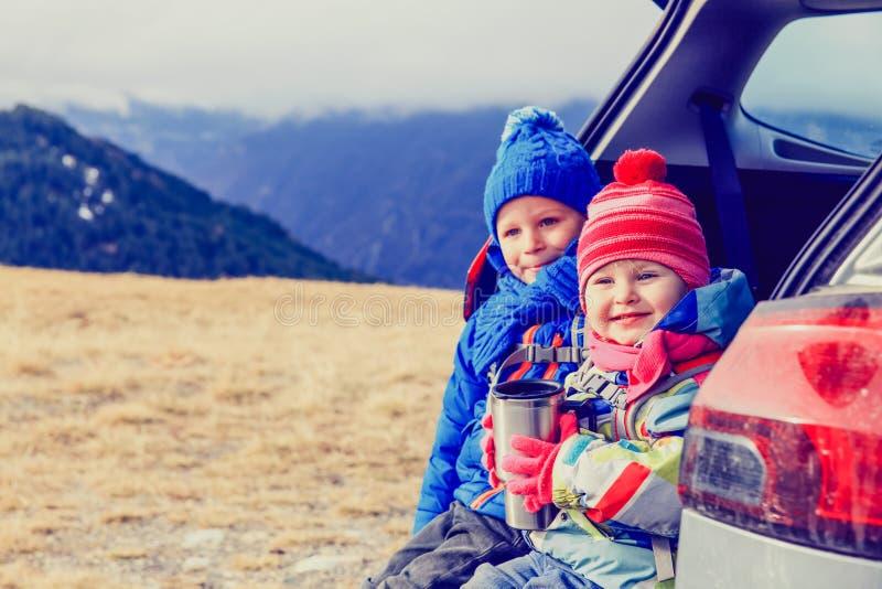 小男孩和女孩乘在山的汽车旅行 图库摄影