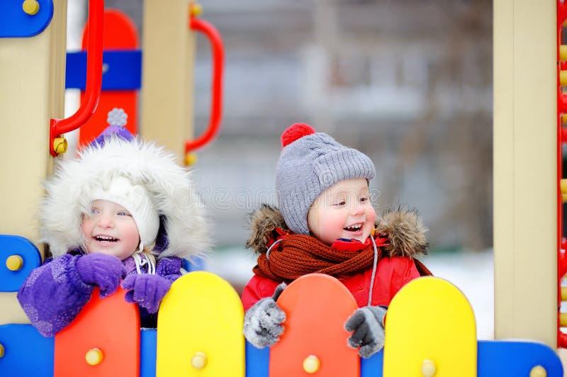 小男孩和女孩冬天衣裳的获得乐趣在户外操场 免版税图库摄影