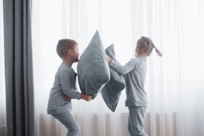 小男孩和女孩在卧室演出了在床上的枕头战 淘气儿童敲打枕头 他们喜欢 免版税库存照片