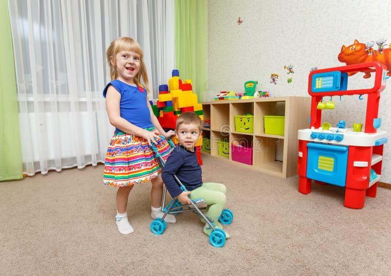 小男孩和女孩在家使用与玩具婴儿推车 免版税库存图片
