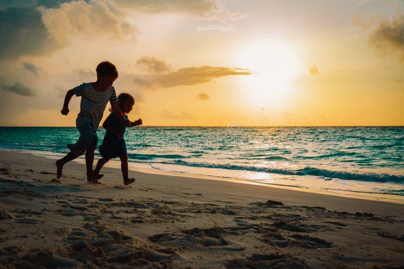 小男孩和女孩在日落海滩的奔跑戏剧 免版税库存图片
