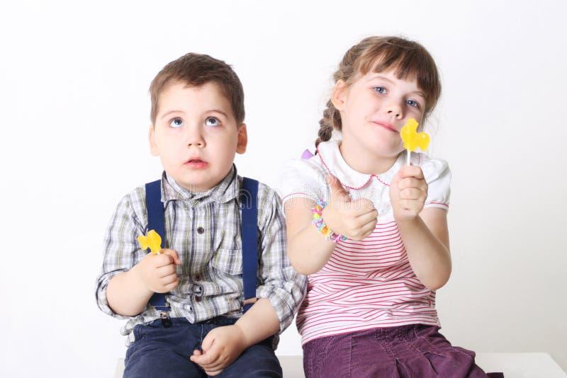 小男孩和女孩坐并且拿着棒棒糖 库存图片