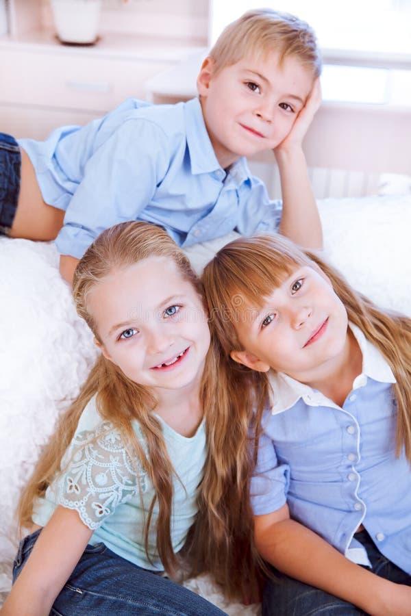 小男孩和女孩坐沙发在dinning的屋子里 库存照片