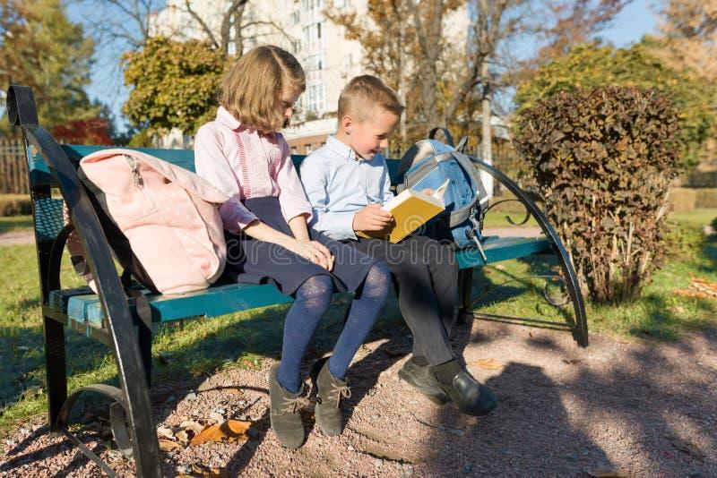 小男孩和女孩学童看书,坐长凳,有背包的孩子 库存照片