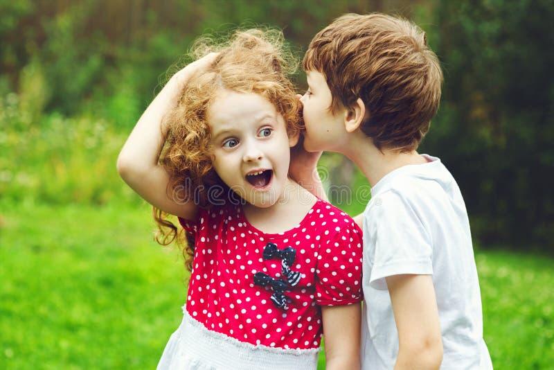 小男孩和女孩耳语 库存照片