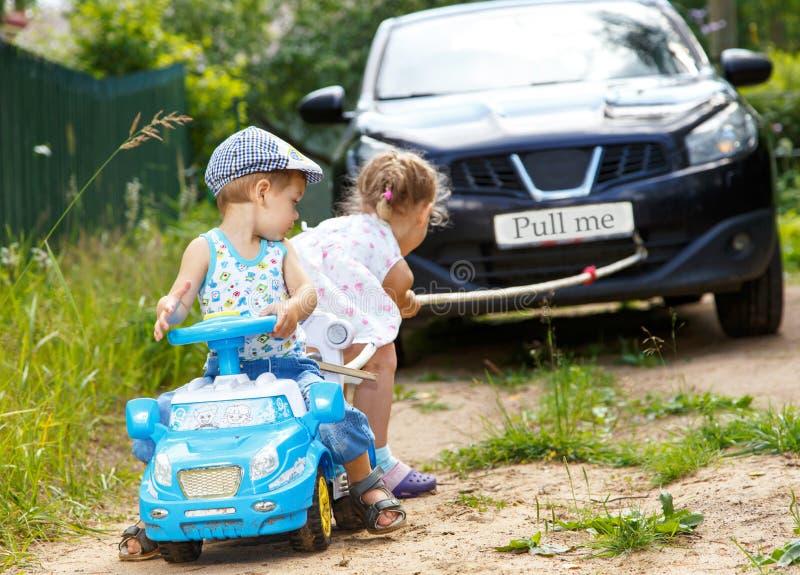 小男孩和女孩要扯拽真正的汽车 库存图片