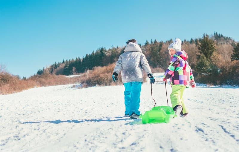 小男孩和女孩运载雪撬和享受冬天sledd 库存照片