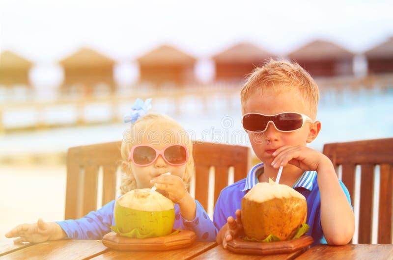 小男孩和女孩饮用的椰子鸡尾酒  免版税库存图片