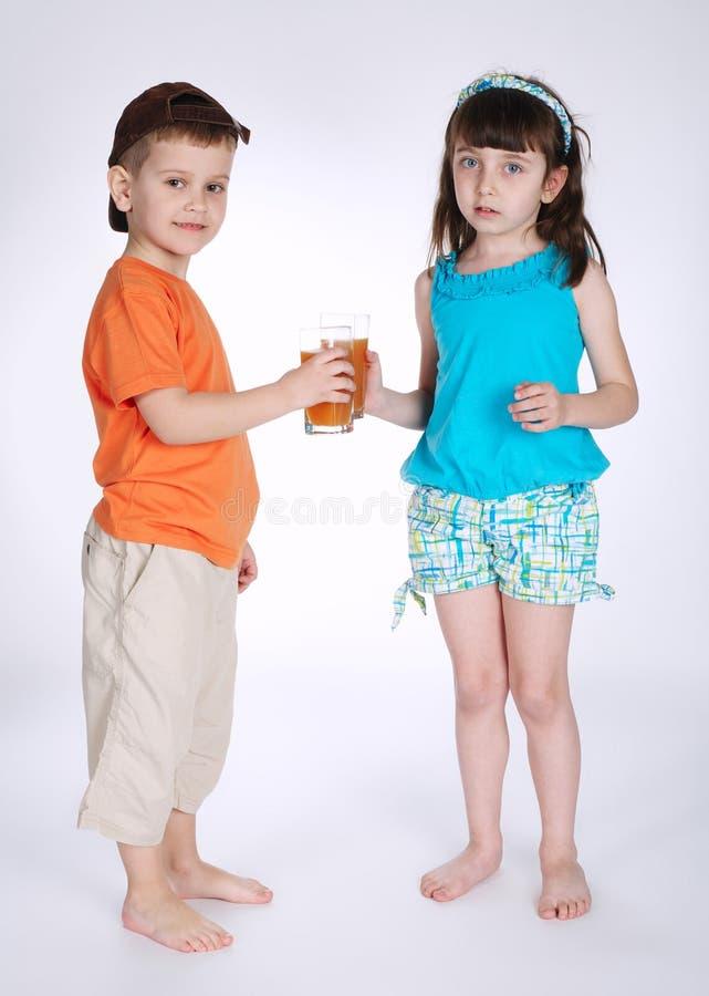 小男孩和女孩饮用的汁液 免版税库存图片