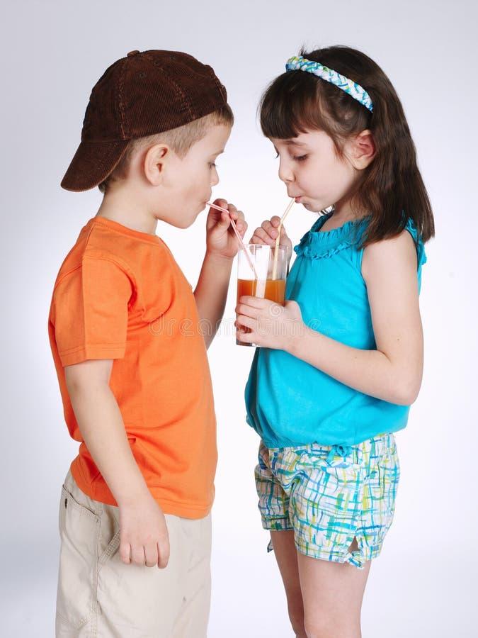 小男孩和女孩饮用的汁液 库存图片