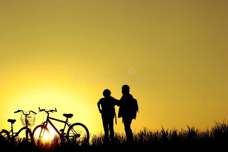小男孩和女孩骑马骑自行车在日落,活跃孩子炫耀,亚洲孩子,现出轮廓孩子在日落,愉快的时间 免版税库存图片