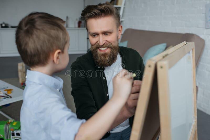 小男孩和微笑的父亲有粉笔的图画图片在黑板 免版税库存照片