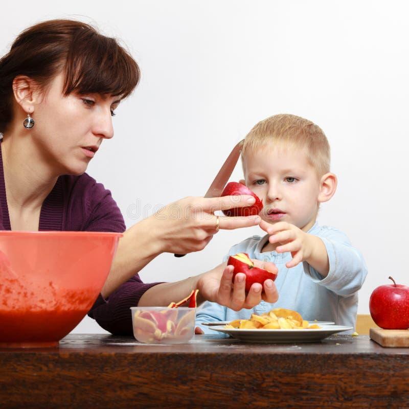 小男孩和母亲与刀子的削皮苹果 库存照片