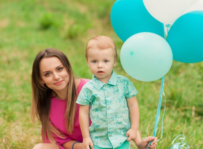 小男孩和母亲春天自然的与五颜六色的气球 免版税库存图片