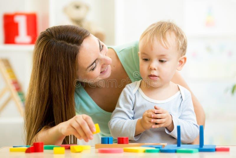 小男孩和母亲有积木的 免版税库存图片
