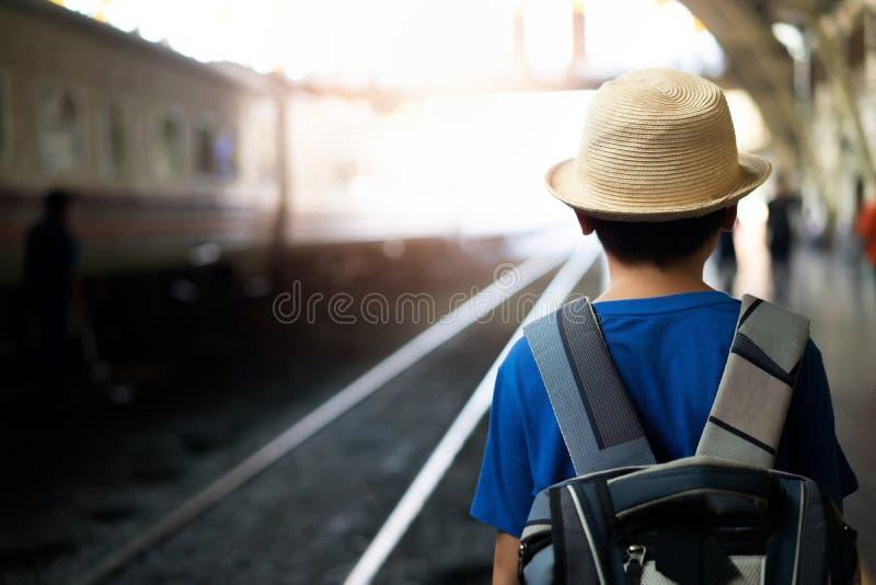 小男孩和背包乘火车移动 免版税库存图片