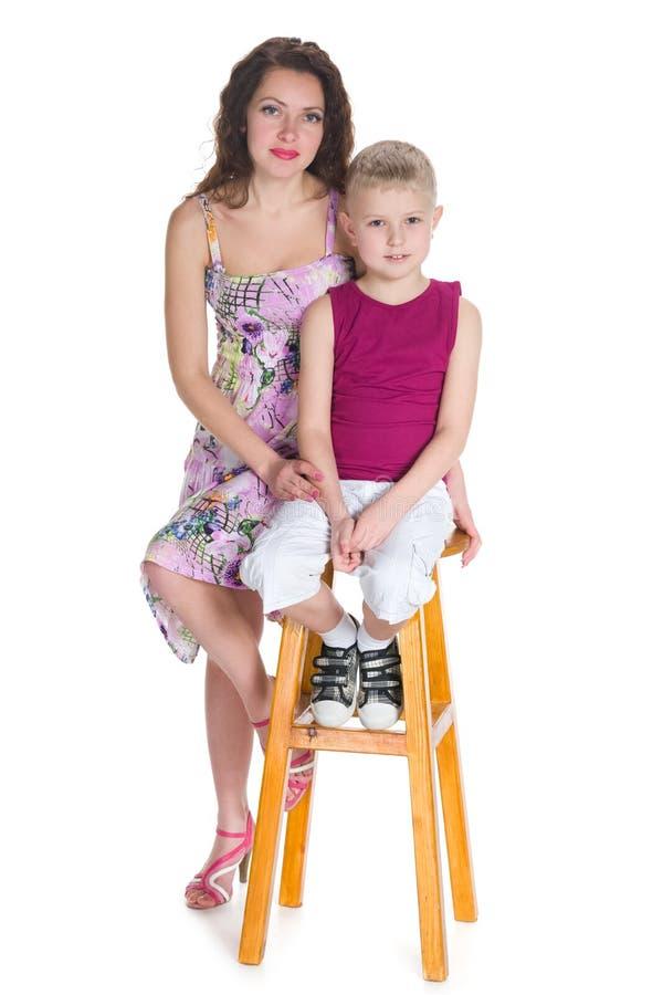 小男孩和他的母亲坐椅子 库存图片