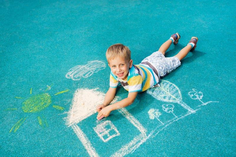 小男孩图画在地面上的白垩图象 免版税库存照片