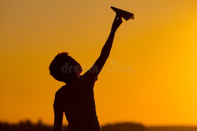 小男孩在他的手上拿着一架纸飞机在日落 孩子培养了他的与origami的手由天空决定和戏剧在 库存照片