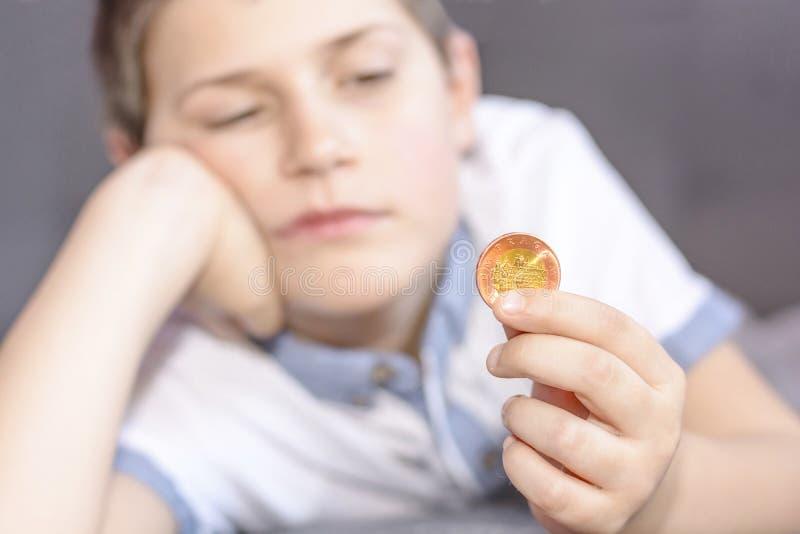 小男孩在他的手上的拿着一枚金属硬币 免版税库存图片