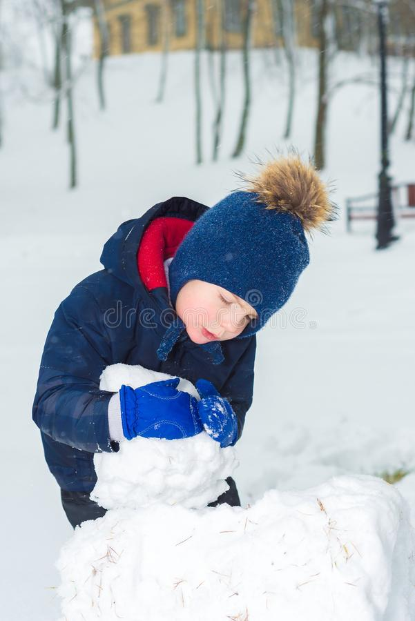 小男孩在冬天 孩子做一个雪人和戏剧 图库摄影