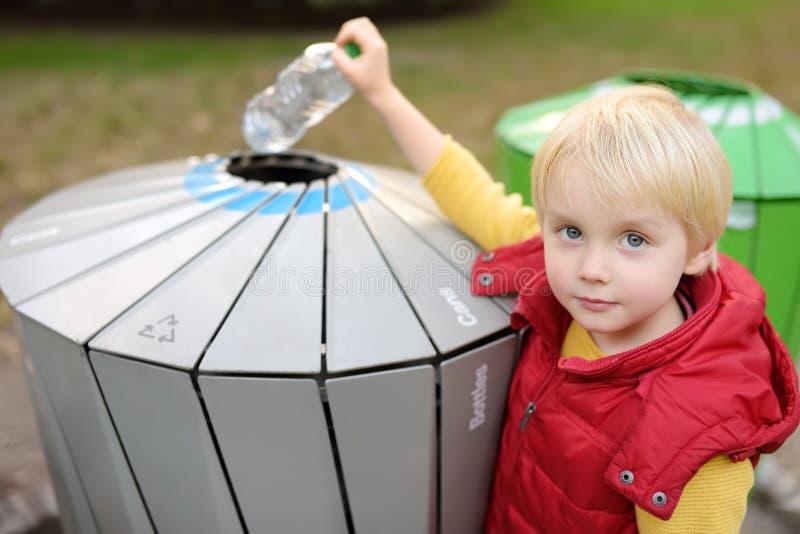 小男孩在分开回收的垃圾箱投入塑料瓶 免版税库存图片