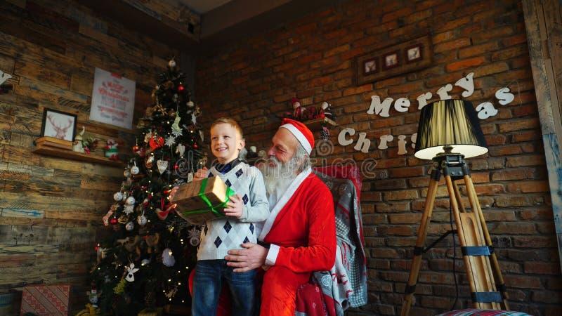 小男孩在圣诞老人s耳朵跑到圣诞老人并且投入欲望 r 免版税图库摄影