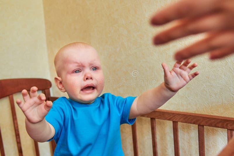 小男孩在小儿床哭泣并且拉扯他的手给妈妈 免版税库存图片