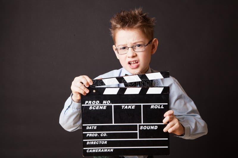 小男孩在手上的拿着拍板。 免版税库存图片