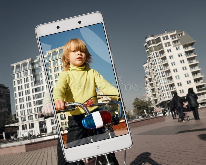 小男孩在智能手机的屏幕上的骑马自行车 库存图片
