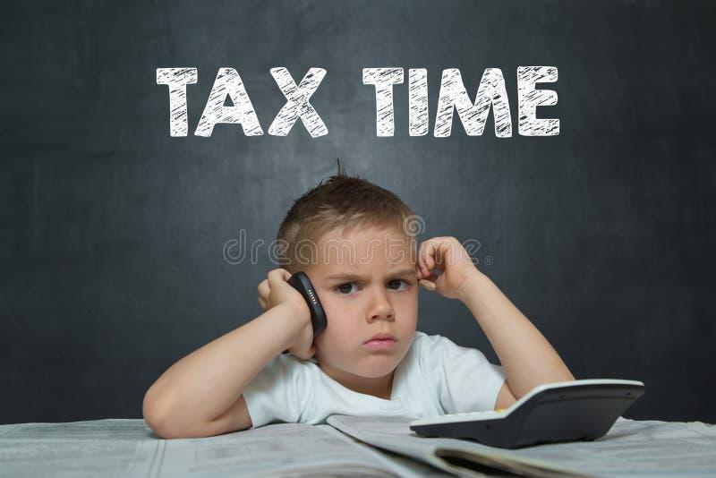 小男孩在有报纸的办公室喜欢商人 免版税库存图片
