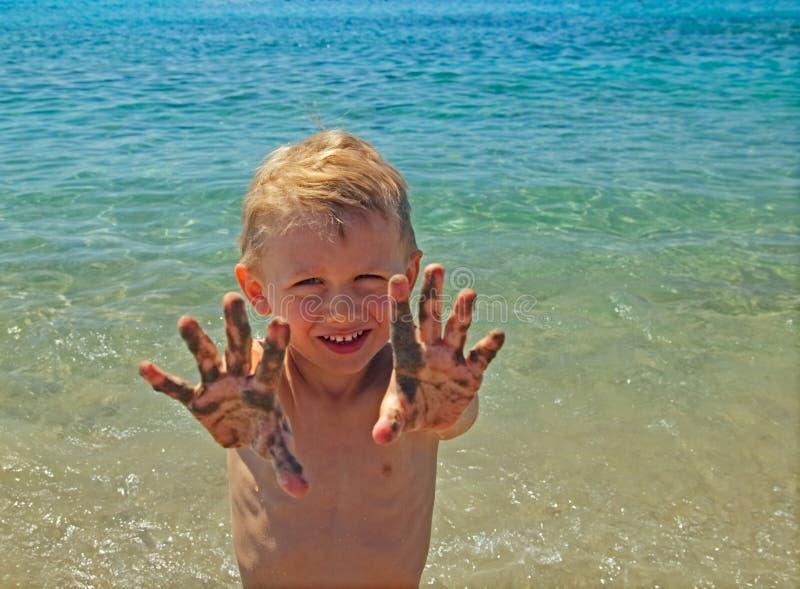 小男孩在沙子显示棕榈 免版税库存图片