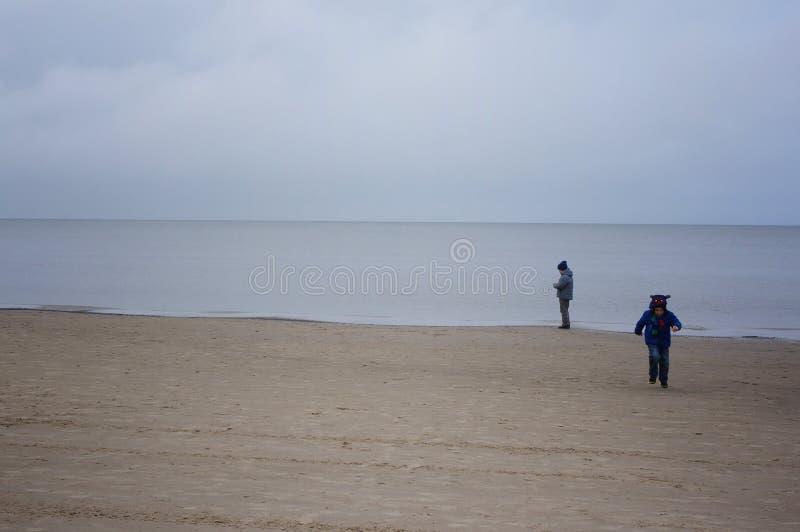 小男孩在海滩站立海在冷的大风天 免版税库存照片