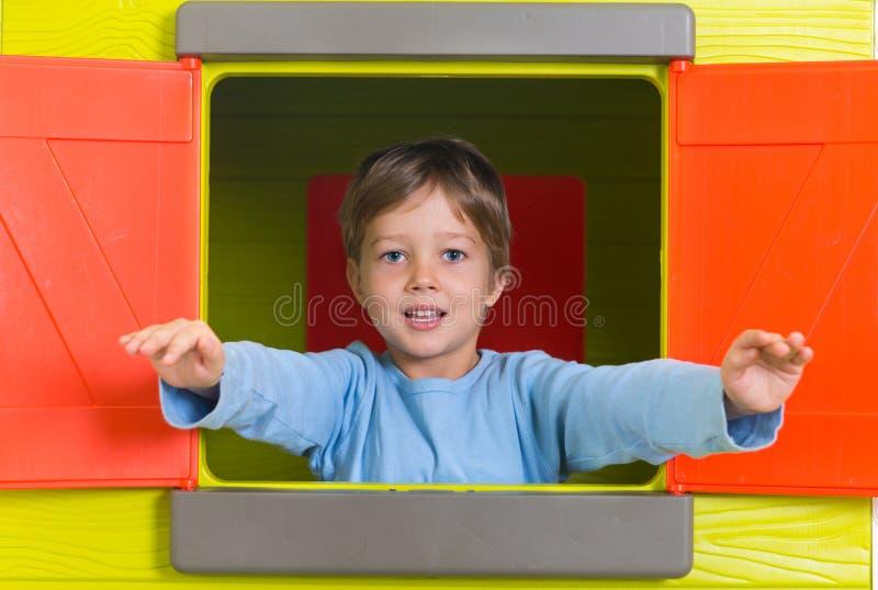小男孩在玩具房子窗口里 免版税图库摄影