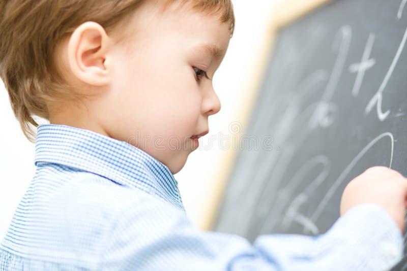小男孩在黑板书写 免版税库存照片