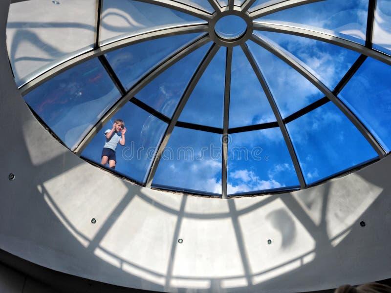 小男孩在玻璃圆屋顶附近站立并且通过玻璃看反对蓝天 免版税库存图片