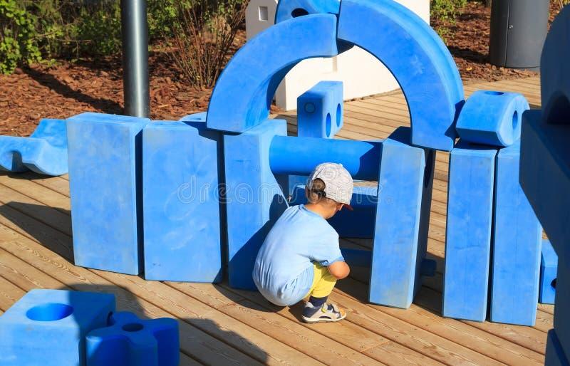 小男孩坐儿童的游乐场在有蓝色巨型几何图的公园想象力的发展的和 免版税图库摄影