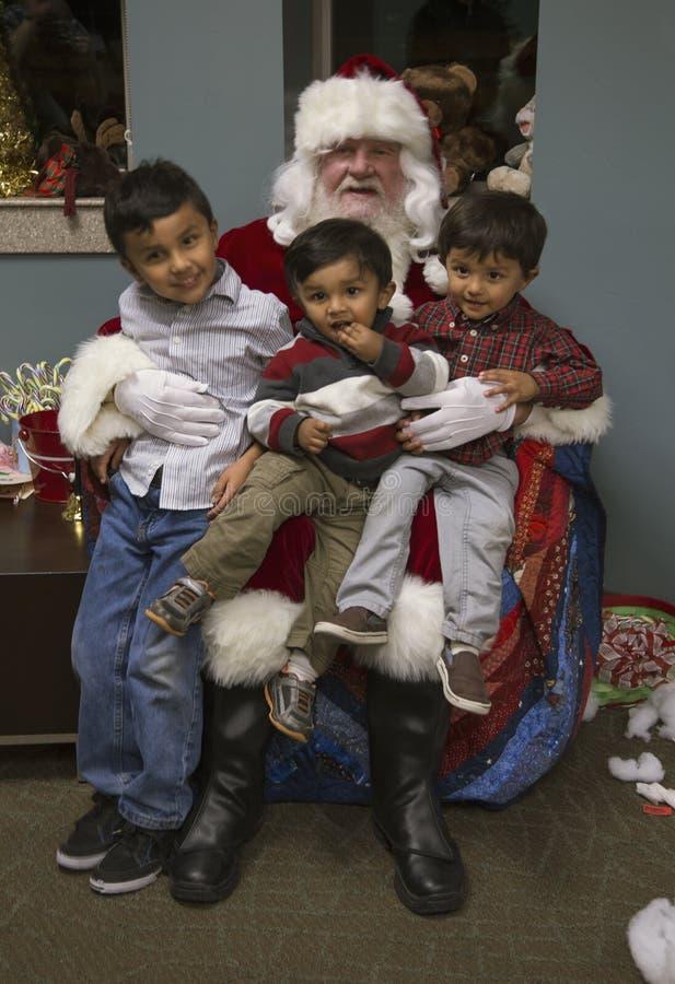 小男孩坐圣诞老人的膝部在美国战士的圣诞晚餐在受伤的战士中心,彭德尔顿营,在圣地亚哥北部, 免版税库存照片